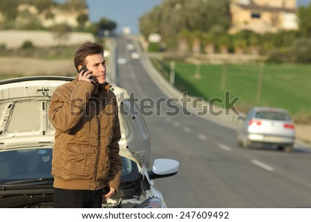 Happy man calling roadside assistance for his breakdown car in a country road - stock photo