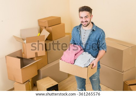 Happy man carrying boxes in new home - stock photo