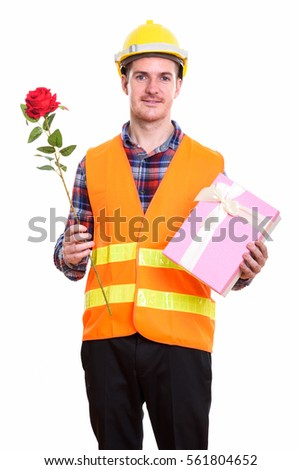 Happy man construction worker smiling while holding red rose and gift box ready for Valentine's day