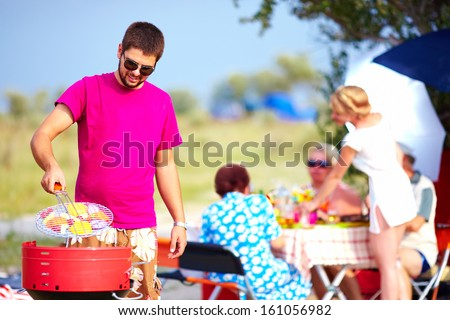 happy man cooks vegetables on the grill, family picnic - stock photo