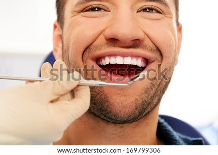 Happy man doing teeth checkup at dentist's surgery  - stock photo