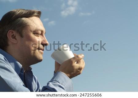 Happy man drinks on nature - stock photo