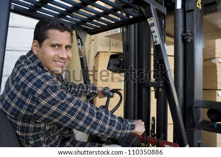 Happy man driving forklift