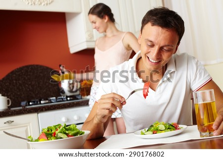 Happy man eating salad with his wife cooking on background