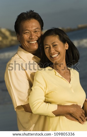 Happy man embracing woman from behind on the beach