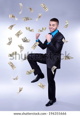 Happy man enjoying rain of money, on grey background
