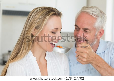 Happy man feeding his partner a spoon of vegetables at home in the kitchen - stock photo