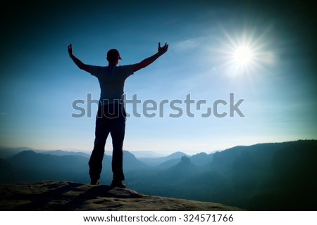 Happy man gesture of triumph with hands in the air. Funny hiker on the peak of sandstone rock in national park Saxony Switzerland  - stock photo
