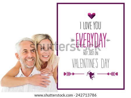 Happy man giving his partner a piggy back against valentines day greeting - stock photo