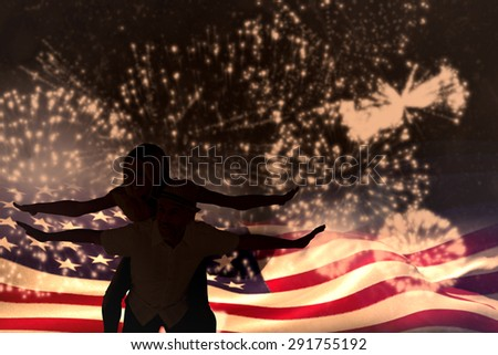 Happy man giving his partner a piggy back against white fireworks exploding on black background - stock photo