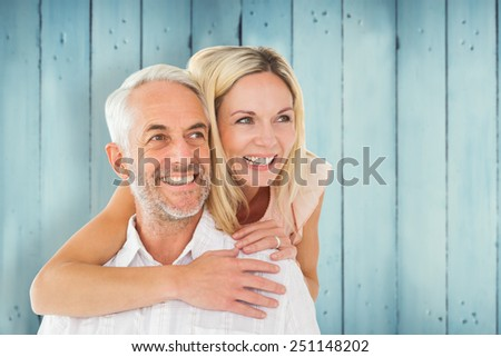 Happy man giving his partner a piggy back against wooden planks - stock photo