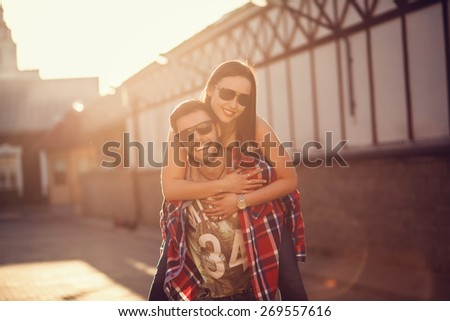 Happy man giving piggyback ride to girlfriend, having fun together - stock photo