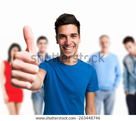 Happy man giving thumbs up in front of a group of people - stock photo