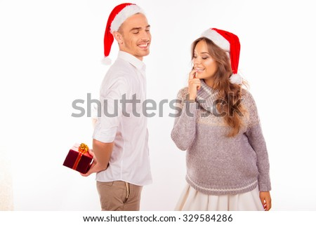 Happy man hid behind his back a Christmas gift for his girlfriend - stock photo