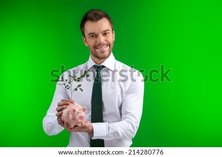 happy man holding bigbank in his hands. businessman place plant into piggy bank on green background - stock photo