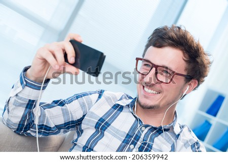 Happy man holding cellphone during video call - stock photo