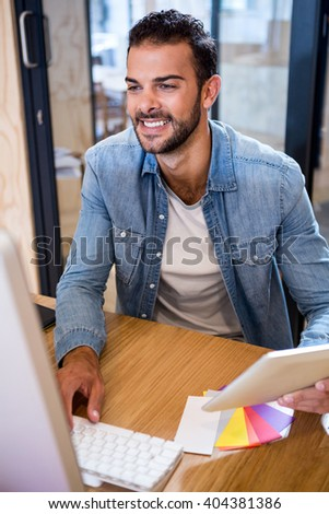Happy man holding digital tablet and using computer in office - stock photo