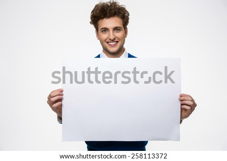 Happy man holding empty paper and looking at camera - stock photo
