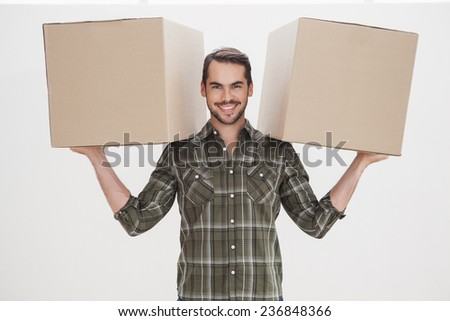 Happy man holding moving boxes at home in the living room - stock photo