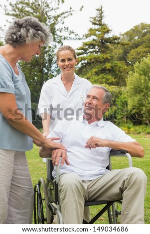 Happy man in a wheelchair talking with his nurse and wife in the park on sunny day