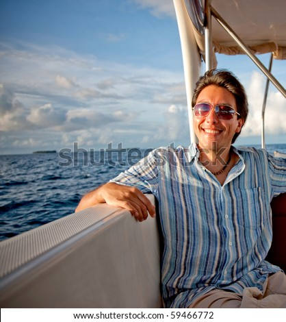 Happy man in a yacht or sailing boat enjoying life - stock photo