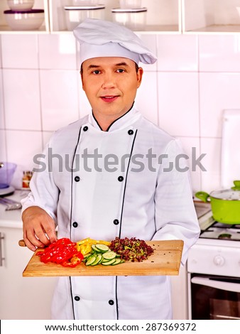 Happy man in chef hat cooking salad . - stock photo