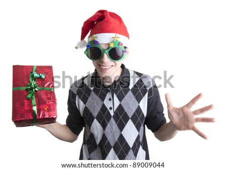 Happy man in Christmas party glasses and hat holds red gift box