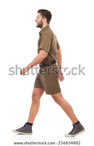 Happy man in khaki uniform walking. Full length studio shot isolated on white. - stock photo