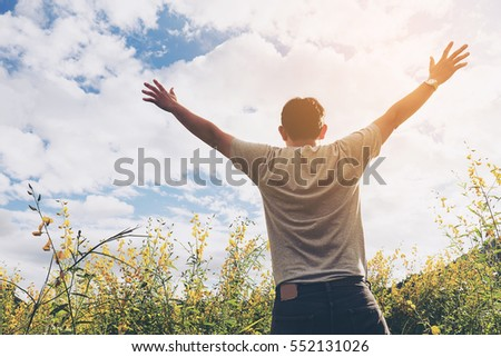 Happy man in nature of yellow field flower and bright sky white cloud