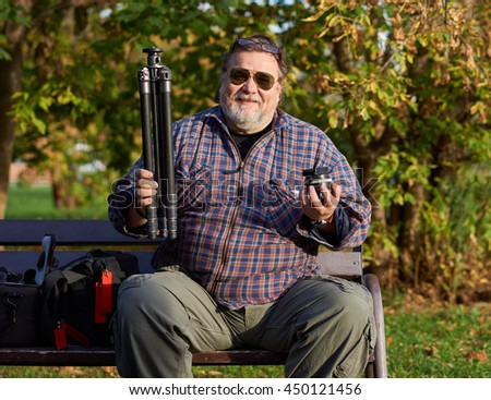 Happy man in sun glasses sits on the bench in the park holding tripod in one hand and ball-head in the other