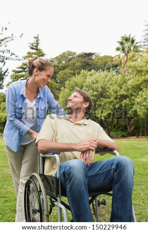 Happy man in wheelchair talking with partner in the park on a sunny day
