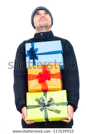 Happy man in winter jacket holding Christmas gift boxes and looking up, isolated on white background.