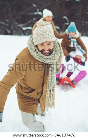 Happy man in winter-wear riding his son and daughter on sledge in winter