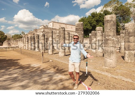 Happy man inviting you to visit the ruins in Chichen Itza, Mexico. - stock photo