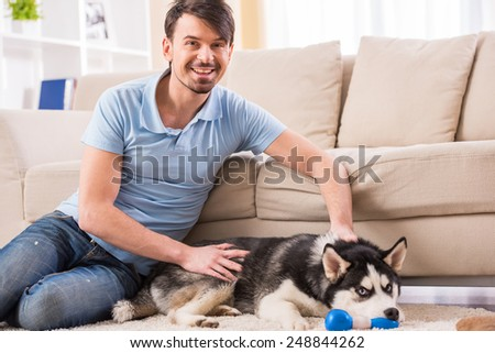 Happy man is playing with his dog at home. - stock photo