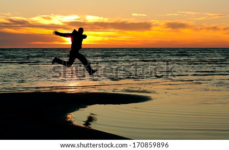 happy man jump on a beach at sunset