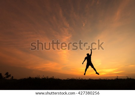 Happy man jumping for joy on the hill, cliff at sunset. Success, winner, happiness