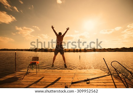 Happy man jumping on pier with lake and sky in background, sunset warm light - stock photo