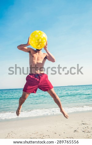 Happy man jumping on the beach on a sunny day - stock photo