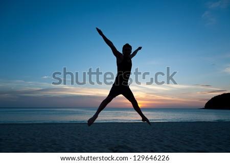 Happy man jumping on the beach on the background of sea