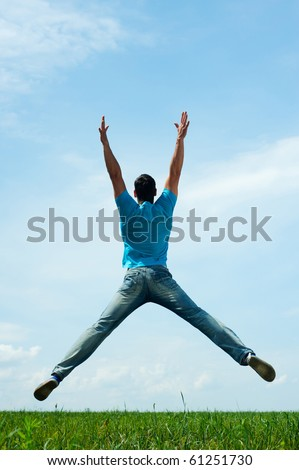 happy man jumping on the field - stock photo