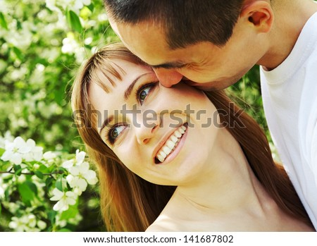 Happy man kissing his girlfriend outdoor - stock photo