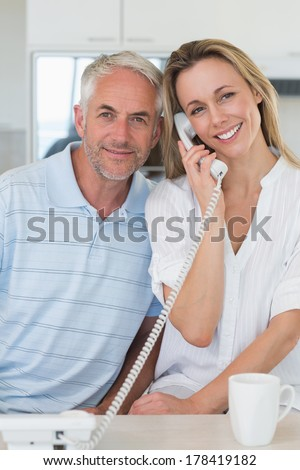 Happy man listening in on his blonde partners phone call at home in the kitchen - stock photo