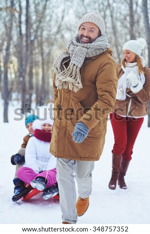 Happy man looking at camera while riding two children on sledge