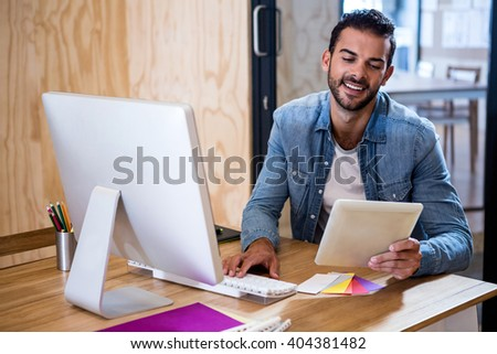 Happy man looking at digital tablet while using computer in office - stock photo