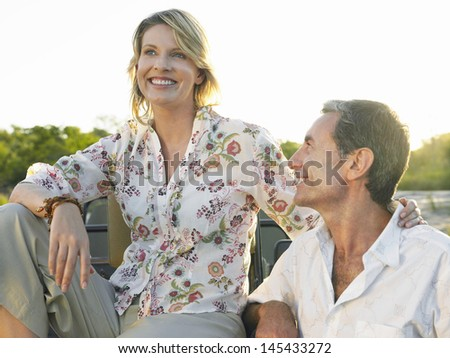 Happy man looking at smiling woman couple sit on jeep - stock photo