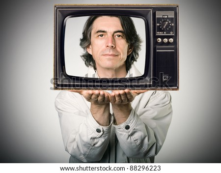 Happy man looking out of a retro television, holding it in his hands.
