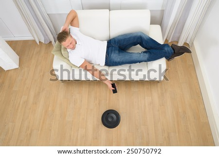 Happy Man Lying On Sofa Operating Robotic Vacuum Cleaner With Remote Control