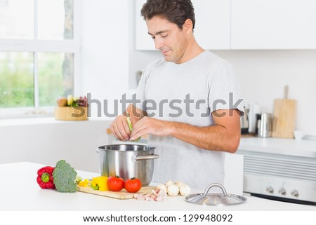 Happy man making dinner in kitchen