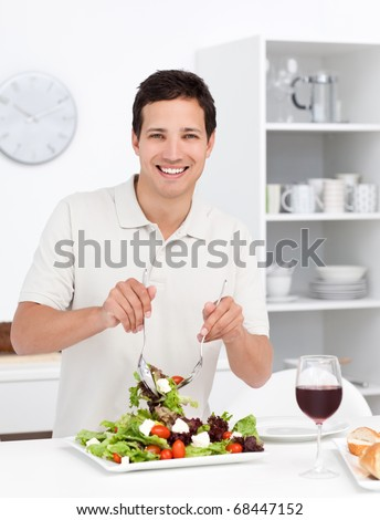 Happy man mixing a salad standing in the kitchen at home - stock photo